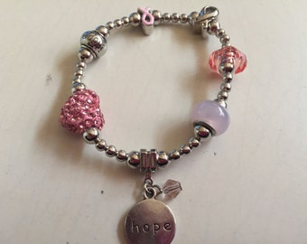 Elastic breast cancer awareness bracelet with charm