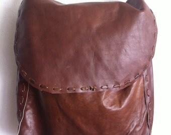 Brown big shoulder bag on a long strap, a bag made of genuine leather.