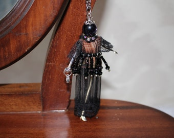 Doll pendant on a chain.