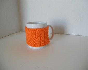 Orange crochet cup cozy with a orange button, crochet mug cozy