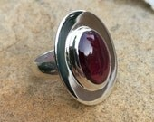Broad faced sterling silver ring with deep pink oval garnet cabochon