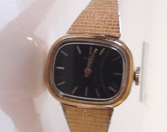 "Ladies Watch 18k gold plated Timex Wind up 1960s Porcelain Face Black Will fit petite wrist from 5"" to 6"" Working"