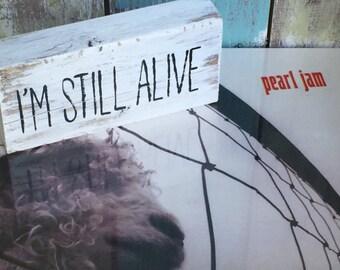 Pearl Jam, shelf block, I'm still alive, Eddie Vedder, quote, music, song lyric, sign, strength, survivor, motivation