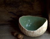 Round organic pinch pot bowl with seafoam green interior.