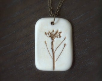 Joy - An earthy porcelain pendant with impression of a tiny flower.