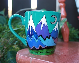 """J.R.R. Tolkien """"The Road goes ever on and on"""" LOTR literary quote mug - Hand painted, large aqua mug with Hobbit style cover art mountains"""