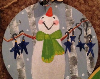 Christmas ornaments set if two snowman with silver bells.  Christmas saying on the back