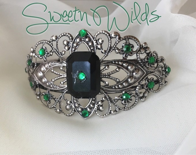 Vintage style antique cuff bracelet with emerald-like gems.