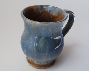 GLossy blue speckled on brown stoneware pottery Lisa mug. Stoneware is durable microwave and dishwasher safe.