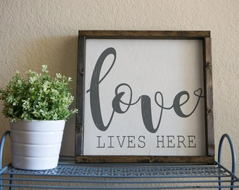 love lives here. 13.5x13.5 distressed wood sign. white with gray writing.