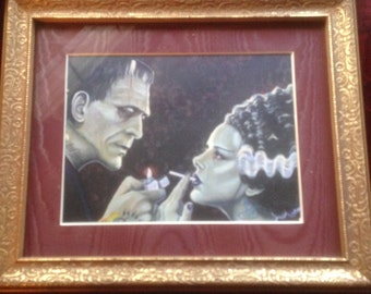 FRANKENSTEIN   lighting cigarett for his bride print framed in a gold filagree frame that hangs on a wall
