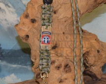US Army Operational camo pattern (OCP) camo parachute cord lanyard with the US Army 82nd Airborne emblem engraved stainless steel charm.