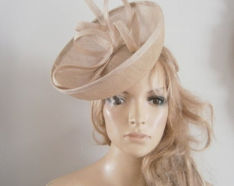 front facing upturned brim,perching saucer in caramel  coloured sinamay embellished with hand sculptured sinamay ribboned strips & loops