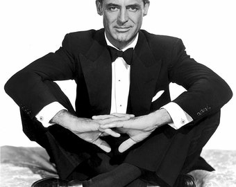 Photo of actor Cary Grant sitting cross-legged in a tux