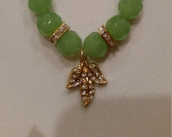 Jade colored bead bracelet with gold charms