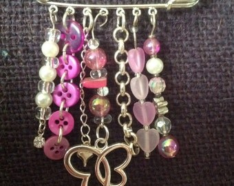 Silver kilt pin brooch with pink beads, buttons and a butterfly pendant