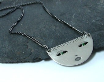 Half round face, silver pendant with green eyes.