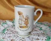 Vintage Holly Hobbie Porcelain Pedestal Footed Coffee Cup / Mug 1973 - Love is the little things you do - flower green trim *eb