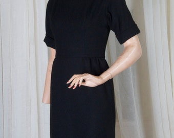 Black wool blend, knit short sleeved dress w boatneck collar by Craig. 1970s,