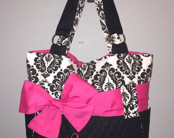 Personalized Black And White Damask Diaper Bag With Hot Pink Bow And Black Quilt. Added Outside Bottle Pockets. Add Matching Accessories