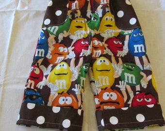 M&M print pants with brown polka dot pockets and cuff