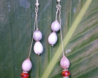 Earrings of JOBS TEARS and faceted orange carnelian beads hung from sterling silver wire.