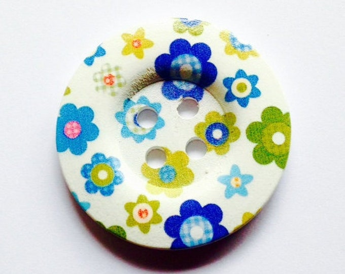 50mm button featuring different types of green and blue flowers.