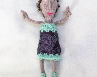 Hand Knitted Doll Wearing a Pretty Purple and Green Dress