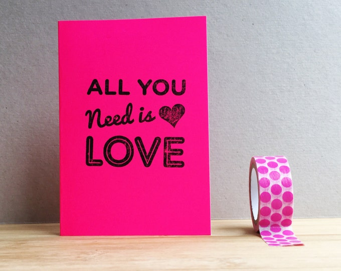 All you need is love hand printed typographic mini greetings card in neon pink