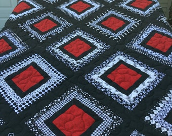 This is a handsewn queen size quilt featuring red black and white fabrics.