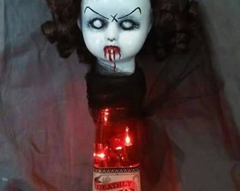 Miss Annie that sits upon her very own red bottle that lights up. Zombie doll, creepy doll, Halloween doll, haunted doll