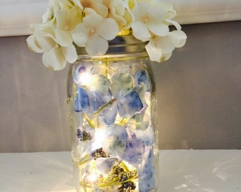 Wide mouth mason jar led light filled with flower petals and topped with hydrangea