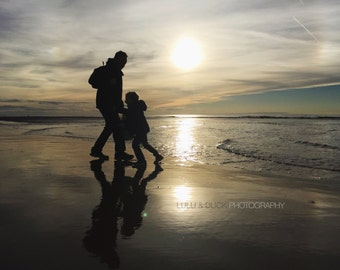 Father and son playing on the autumn beach at sunset