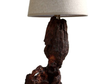 Unique table lamp made of a weathered tree stump on a natural stone foot.