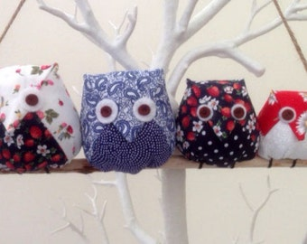 Owl family on a branch, 4 red,blue and white owls