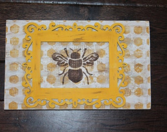 White and yellow wooden sign with a yellow frame and brown image of a bee
