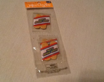 Tasty snack cakes, scrapbook embellishments.  3 packs of snack cakes in one package.