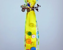 """18"""" Easter Greek Candle Lambada Decorated with Yellow Ribbons, buttons and a metal pin with a flower carriage"""