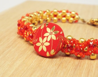 Red and gold woven seed bead bracelet with flower button focal centerpiece