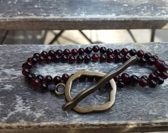 Hand knotted red glass bead choker with brass toggle clasp