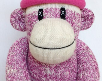 Pretty deep pink traditional style Sock Monkey with a pink striped pom pom hat