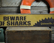Beware Of Sharks Wood Sign, Personalized Beach Location Sign, Distressed Shark Lover Decor - Rustic Hand Made Vintage Wooden Sign ENS1001245