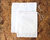 12 6X8 cloth drawstring bags with red stitching