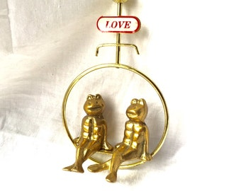 BRASS Frogs on SWING under Love Sign   Two Darling Brass Frogs holding hands on bench