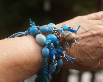 Bracelet made of Three Blue & Turquoise Knotted Hemp Strands Woven Together with Glass and Wood Beads and Gold Tone Metal Findings