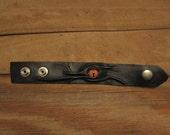 Grichels leather wrist cuff/bracelet - black with poppy orange slit pupil reptile eye