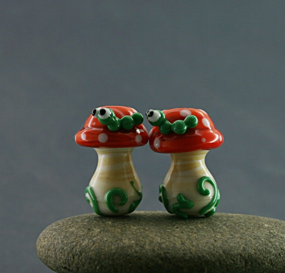 Two toadstool glass lampwork beads with green worms or ladybugs
