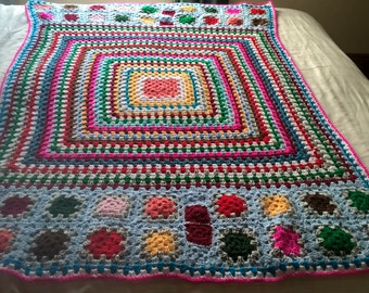Multi coloured granny square throw. Handmade crochet afghan blanket.Bright and cheerful. Measures 134x100cms (53x40cms). Cosy snuggle cover.
