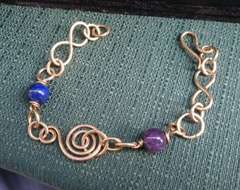 Hammered brass bracelet cord and infinity with Lapis and Amethyst.