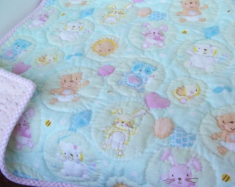 Flannel baby quilt with pink minky backing.  Mint green background with hand quilted designs of bunnies, bears, chicks. FREE SHIPPING!